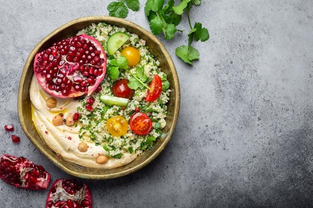 Rustikale schüssel mit couscous-salat mit gemüse, hummus und frisch geschnittenem granatapfel. mahlzeit im nahöstlichen oder arabischen stil mit gewürzen und frischem koriander. gesundes mediterranes abendessen, platz für text