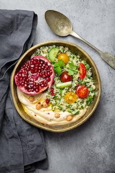 Rustikale schüssel mit couscous-salat mit gemüse, hummus und frisch geschnittenem granatapfel. mahlzeit im nahöstlichen oder arabischen stil mit gewürzen und frischem koriander. schönes und gesundes mediterranes abendessen