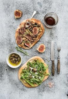 Rustikale selbst gemachte pizzen mit aubergine, käse, oliven, arugula, prosciutto und feigen über schmutztabelle. ansicht von oben.