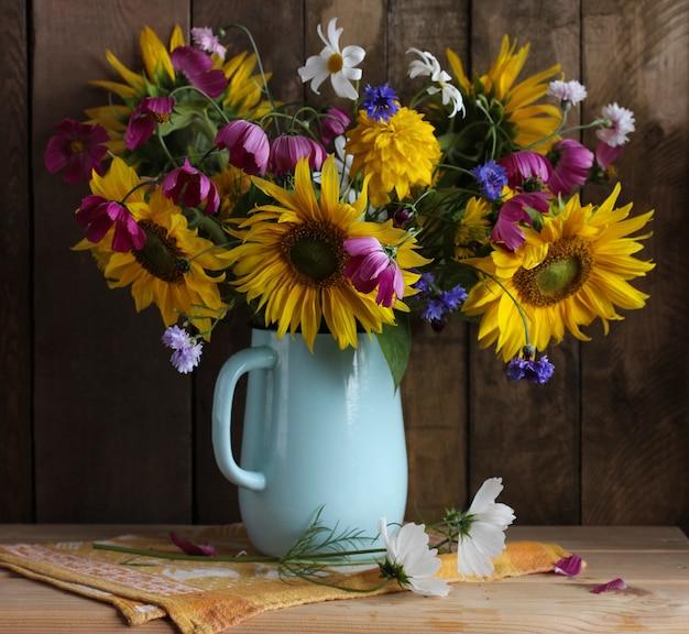 Rustikale sommerkomposition mit einem blumenstrauß in einem emaillierten krug sonnenblumen