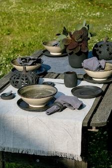 Rustikale tischdekoration draußen im garten mit leerem keramikgeschirr