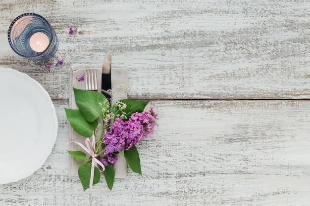 Rustikale tischdekoration mit lila blumen auf hellem holztisch