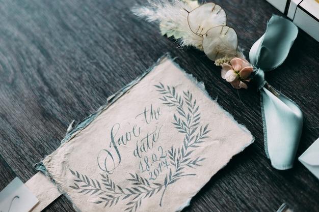 Rustikale und grafische hochzeit der schönen kalligraphiekarten mit blumen- und chiffonspulen. schöne hochzeitseinladung. draufsicht.