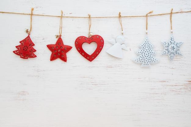 Rustikale weihnachtsverzierung des weihnachtshintergrundmetalls, die am weißen holz- und kopienraumdesign hängt.
