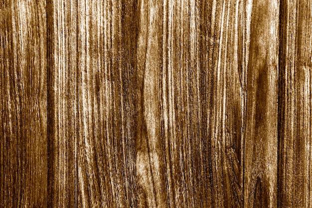 Rustikaler goldbemalter strukturierter holzhintergrund