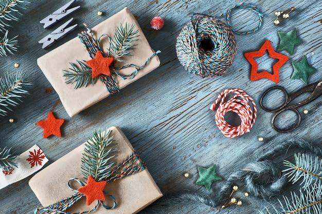 Rustikaler hölzerner hintergrund in grünem und in orange mit tannenzweigen und weihnachtsgeschenken im einfachen braunen packpapier