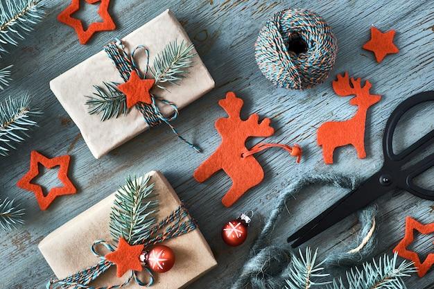 Rustikaler hölzerner hintergrund in grünem und in rotem mit tannenzweigen und weihnachtsgeschenken im einfachen braunen packpapier