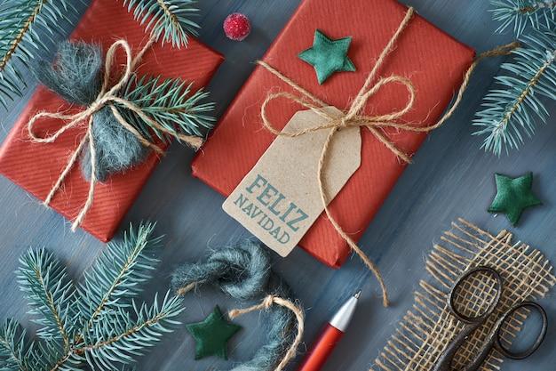 Rustikaler hölzerner hintergrund mit den tannenzweigen und weihnachtsgeschenken geschenk eingewickelt im roten papier