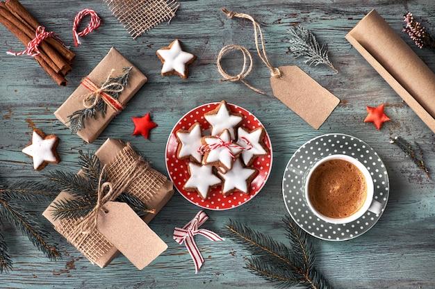 Rustikaler hölzerner hintergrund mit schale heißem kaffee und geschenken