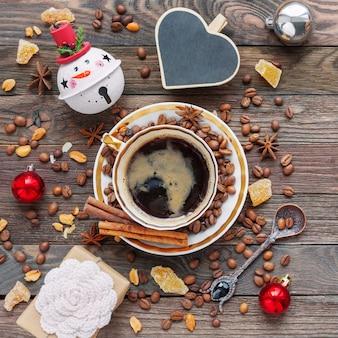Rustikaler hölzerner hintergrund mit tasse kaffee und dekorationen des neuen jahres