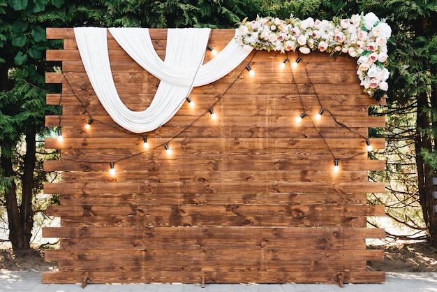Rustikaler hölzerner hochzeitsbogen mit retro-girlande verziert mit blumen für hochzeitszeremonie-jungvermählten