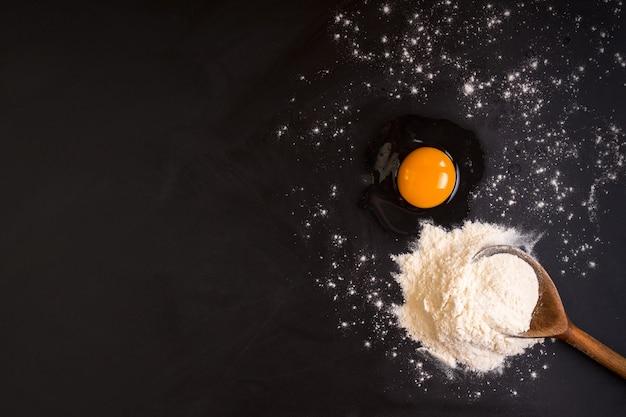 Rustikaler holzlöffel mit einem mehl, einem rohen ei auf einem schwarzen tafelhintergrund. backhintergrund.