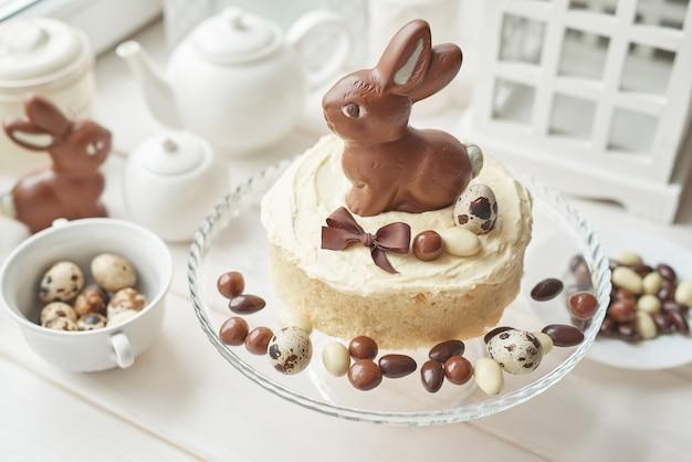 Rustikaler ostern-kuchen mit schokoladenhäschen und -eiern