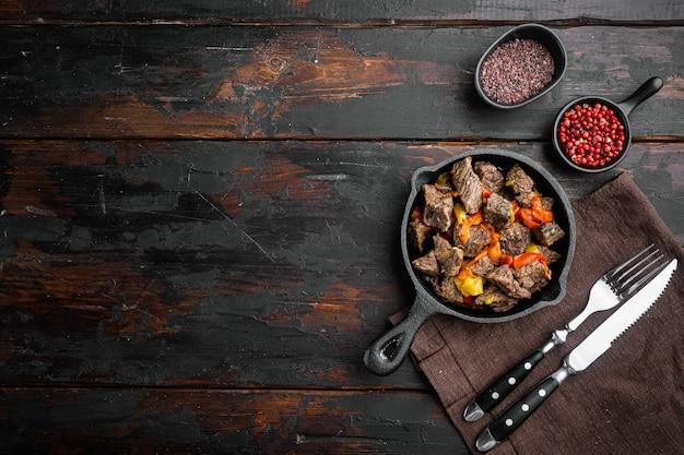 Rustikaler rindfleischgulasch im rustikalen stil in einer gusseisernen pfanne auf einem alten dunklen holztisch