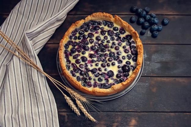 Rustikaler shortbread pie mit blaubeeren in sauerrahmfüllung auf einem holz