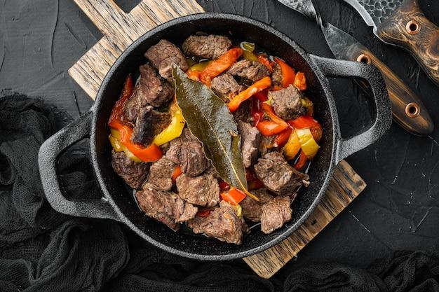 Rustikaler stil des rindfleisch-eintopf-gulasches in der gusseisernen pfanne auf schwarzem stein