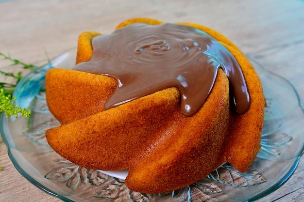 Rustikaler und köstlicher karottenkuchen mit schokoladenbelag auf einem holztisch