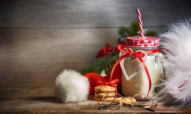 Rustikaler weihnachtshintergrund mit milch und keksen zum weihnachtsmann