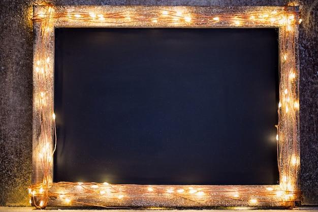 Rustikaler weihnachtshintergrund - vintage planked holz mit lichtern und weihnachtsdekoration.