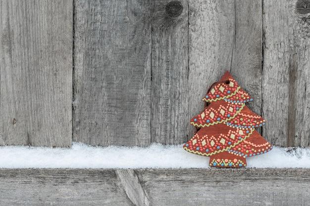 Rustikaler winterhintergrund mit hölzernem weihnachtsbaum