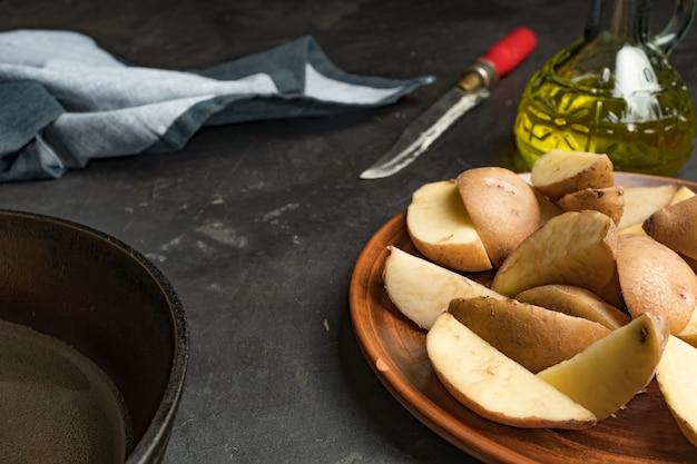 Rustikales essen. bratkartoffeln in einer pfanne auf einem dunklen betontisch. rustikaler stil.
