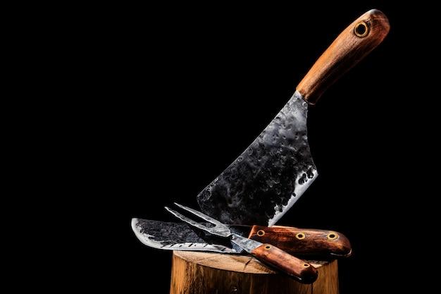 Rustikales fleischfleischmesser, hackmesser und gabel auf schwarz