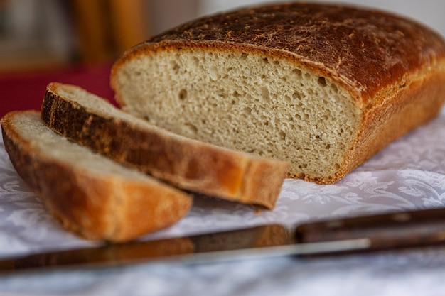 Rustikales frisch gebackenes brot mit geschnittenen scheiben auf einem holztisch. nahansicht.