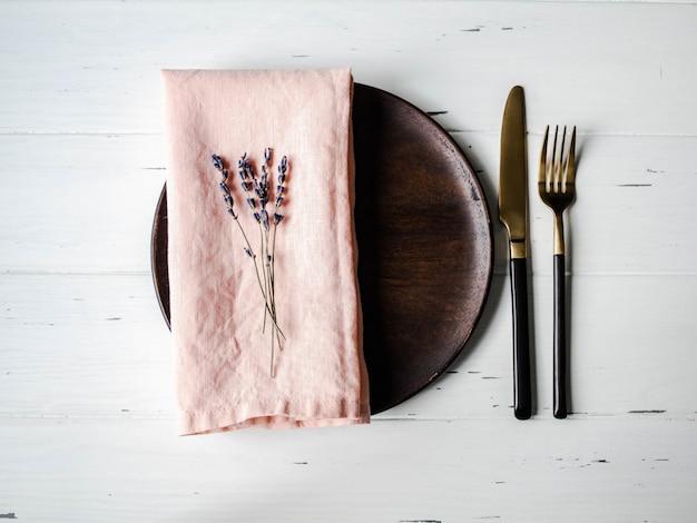 Rustikales gedeck mit platte, rosa serviette, lavendel und geräten auf weißer hölzerner tabelle. ansicht von oben.