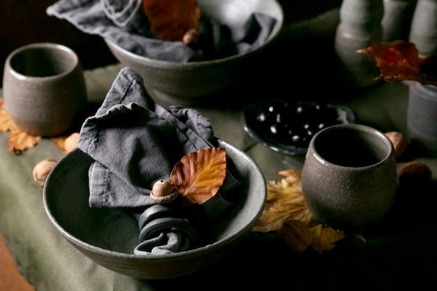 Rustikales herbst-halloween- oder thanksgiving-gedeck mit leerem keramikgeschirr, grauen, rauen schalen und tassen auf leinentischdecke mit herbstgelben blättern und eicheln. dunkler hintergrund