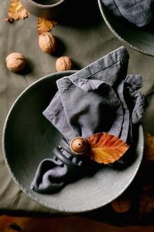 Rustikales herbst-halloween- oder thanksgiving-gedeck mit leerem keramikgeschirr, grauen, rauen schalen und tassen auf leinentischdecke mit herbstgelben blättern und eicheln. flach legen