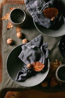 Rustikales herbst-halloween- oder thanksgiving-gedeck mit leerem keramikgeschirr, grauen, rauen schalen und tassen auf leinentischdecke mit herbstgelben blättern und eicheln und nüssen. flach legen