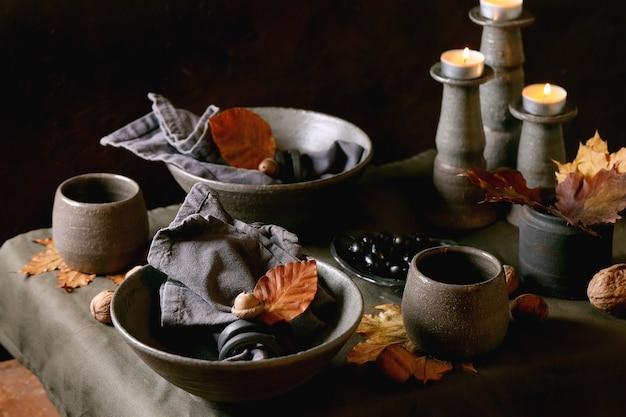 Rustikales herbst-halloween- oder thanksgiving-gedeck mit leerem keramikgeschirr, grauen schalen und tassen, brennenden kerzen auf leinentischdecke mit herbstgelben blättern und eicheln. dunkler hintergrund