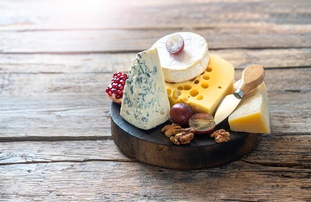 Rustikales käsebrett aus holz mit camembertkäse, parmesankäse, maasdam-käse.