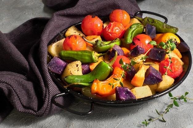 Rustikales, ofengebackenes gemüse in auflaufform. vegetarische vegane saisonmahlzeit auf leichtbeton