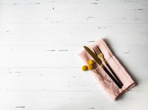 Rustikales romantisches gedeck mit rosa serviette, gelben blumen und geräten auf weißer hölzerner tabelle. ansicht von oben.