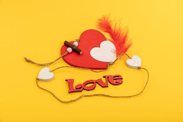 Rustikales rotes herz des valentinstags aus holz auf gelbem hintergrund. liebe in holz, valentinstag konzept.