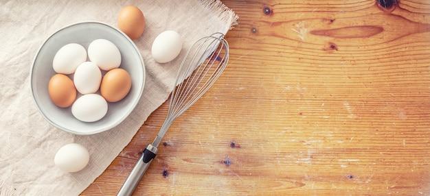 Rustikales schneidebrett und tischdecke mit neun eiern in und aus einer schleife und einem schneebesen aus metall.