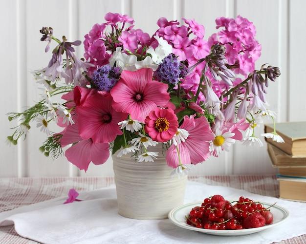 Rustikales stillleben mit blumen und beeren ein strauß rosa blüten phlox lavater kamille hosta ageratum und himbeere rote johannisbeere auf einem teller
