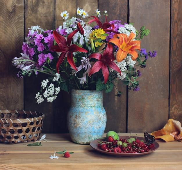 Rustikales stillleben mit blumen und beeren sommerstrauß von phlox-lilien gänseblümchen in einer vase auf einem hölzernen hintergrund himbeeren johannisbeeren stachelbeeren in einem teller auf dem tisch