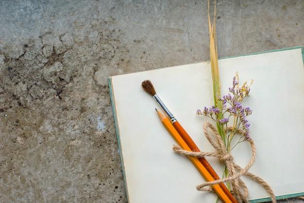 Rustikales weinleseanmerkungsbuch auf rauem konkretem boden, flache lage, copyspace