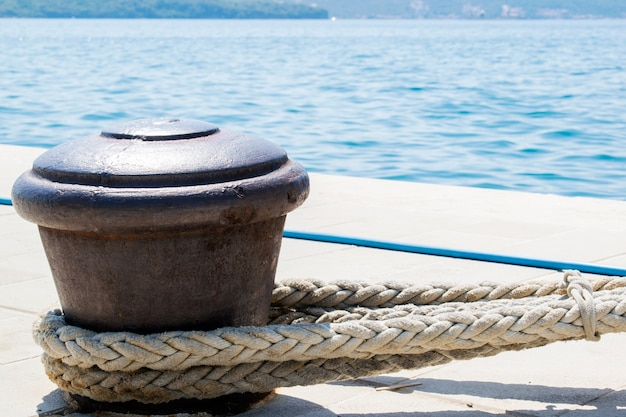 Rusty boat mooring auf einer hafenmauer mit seil befestigt