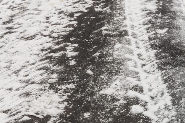 Rutschige straßen. spur vom reifenprofil auf schnee.