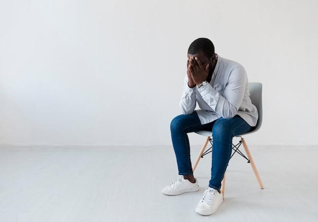 Sa afroamerikanischer mann sitzt auf einem stuhl
