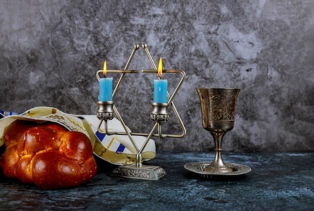 Sabbat-jüdisches feiertagschallahbrot und -candelas auf holztisch