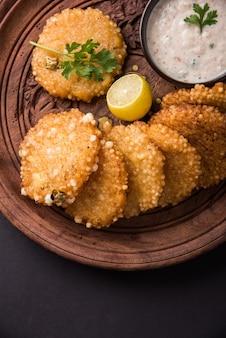 Sabudana oder sago vada ist ein traditioneller frittierter snack aus indien. serviert mit würzigem grün- oder erdnuss-chutney. servieren sie in holzplatte über buntem oder hölzernem hintergrund. selektiver fokus