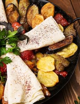 Sac ici, traditionelle kaukasische mahlzeit mit gebratenem fleisch und gemüse, serviert mit lavash