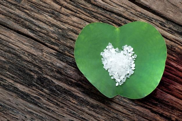 Saccharin- oder süßstoffkristalle auf lotusgrünem blatt und auf einer alten holzansicht von oben, flach gelegen.
