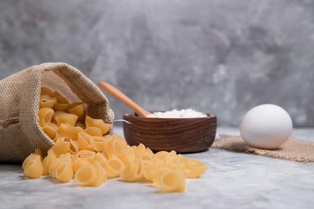 Sack beutel mit getrockneten schalenförmigen makkaroni mit einer holzschale mehl