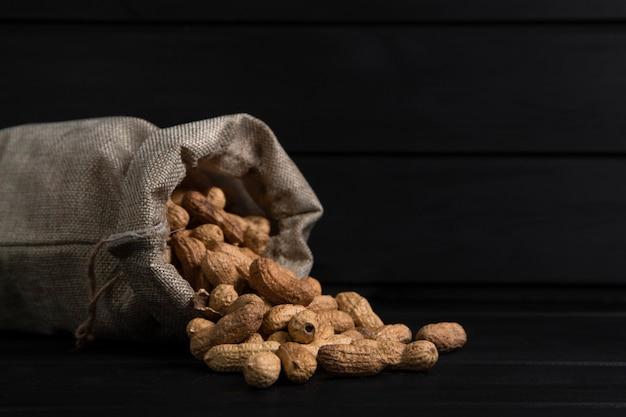 Sack stoff von bio-erdnüssen für die herstellung von butter auf schwarzem hintergrund platziert. hochwertiges foto