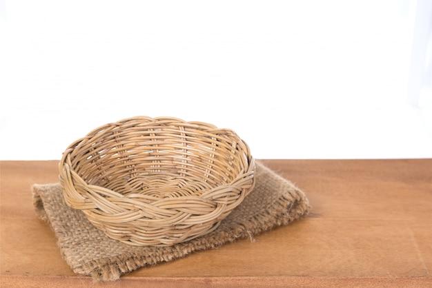 Sackcloth und bambuskorb auf holzhintergrund mit clipping path